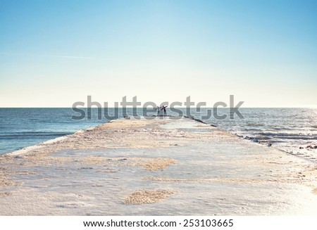 Man and woman standing on the coast - stock photo