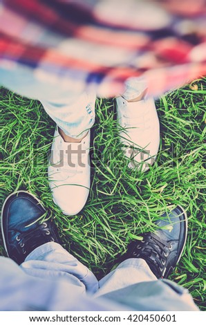 Man and woman standing on the grass close to each other. Women's and men's feet. Top view (vintage) - stock photo