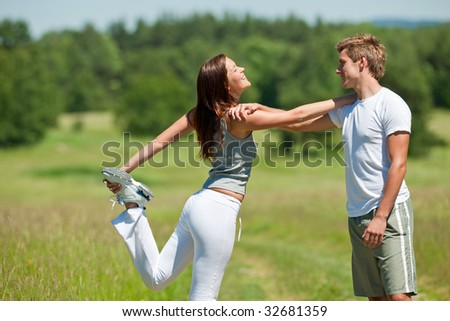 Man and woman stretching in the nature, shallow DOF
