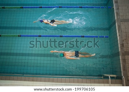 Man and woman swimming in the pool at the leisure center - stock photo