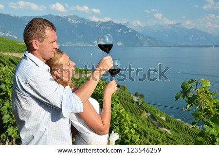 Man and woman tasting wine among vineyards in Lavaux, Switzerland - stock photo