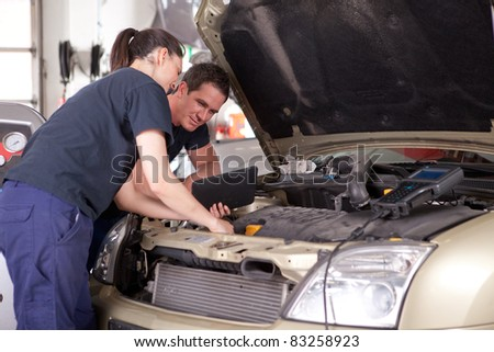 Man and woman team of mechanics using digital tablet while diagnosing car engine. - stock photo