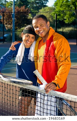 Man and woman tennis players smiling  as they stand at the net. He has his arm around her and they are holding rackets. Vertically framed photo. - stock photo
