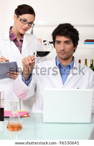 Man and woman testing wine in laboratory - stock photo