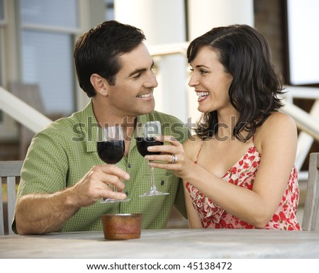 Man and woman toast with red wine glasses at an outdoor cafe. Horizontal shot. - stock photo