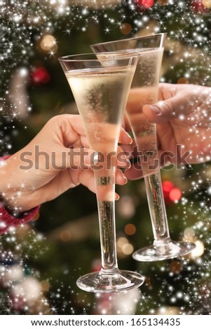 Man and Woman Toasting Champagne in Front of Decorations, Lights and Snow Flake Border. - stock photo