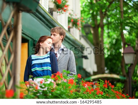 Man and woman together on balcony of their house or hotel with blossoming geranium and nice view - stock photo