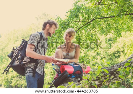 Man and woman tourists backpackers reading map on trip while resting.  Young couple hikers searching looking for direction guide. Backpacking summer vacation travel.
