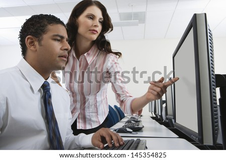Man and woman using computer together - stock photo