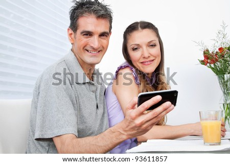 Man and woman using Social Networking with smartphone at breakfast - stock photo