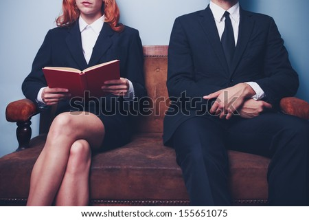 Man and woman waiting to enter a job interview - stock photo