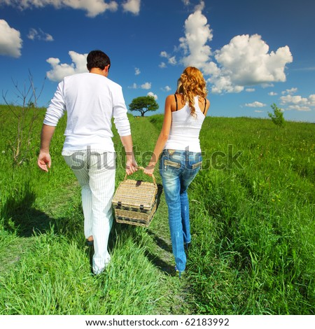man and woman walk on picnic