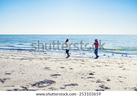 Man and woman walk on the beach - stock photo