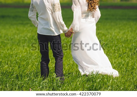man and woman walking in green field - stock photo