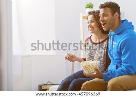 Man and woman watching tv on couch - stock photo