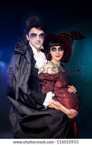 man and woman  wearing  as  vampire and  pregnant witch. Halloween., Joke - stock photo