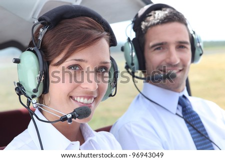 Man and woman wearing headsets in the open cockpit of a light aircraft - stock photo