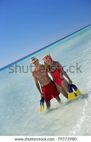 Man and woman wearing red swimsuits standing in clear waters in the Gulf.