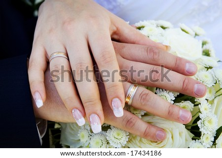 Man and woman wedding hands with the flowers bouquet