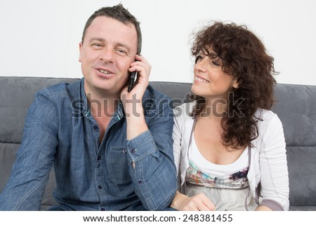 Man and woman with a phone at home - stock photo
