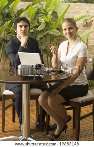 Man and woman with a projector and a laptop.. They are seated and she is smiling while he looks pensive. Vertically framed photo. - stock photo