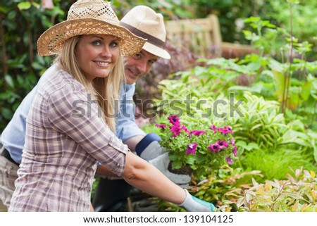 Man and woman with hats and gloves are working in the garden - stock photo