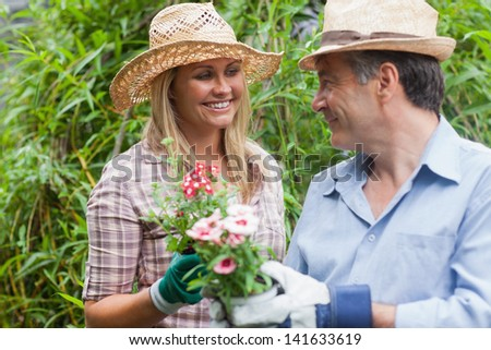 Man and woman with hats are smiling at each other while holding a flower pot - stock photo