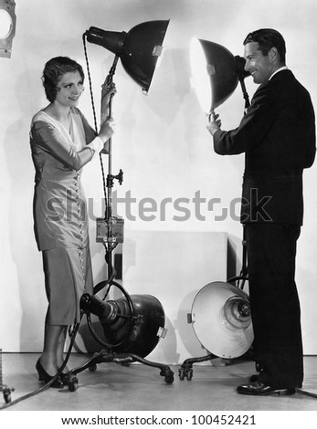 Man and woman with lights on stands - stock photo