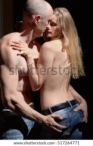Man and woman with naked torsos stand embracing spotlighted in dark room.