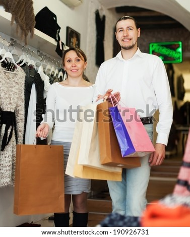 Man and woman with shopping bags at fashion shop