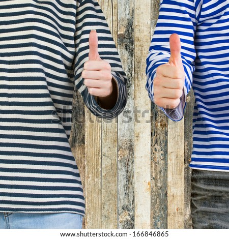 Man and woman with thumbs up sign over wooden background with copy space. Young couple showing thumbs up sign - stock photo