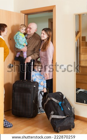 Man and woman with two children coming to grandmother  home - stock photo