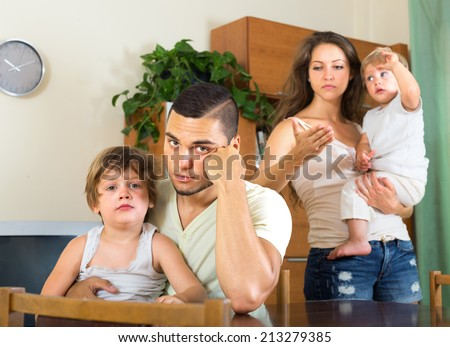 man and woman with two children quarreling at home