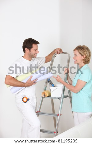 man and woman with wallpaper rolls - stock photo