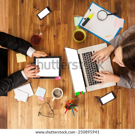 Man and woman working on laptop and tablet. Shot from above view - stock photo