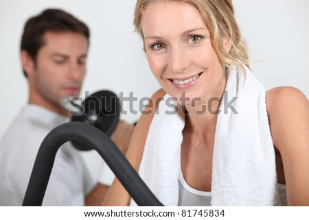 Man and woman working out in gym - stock photo