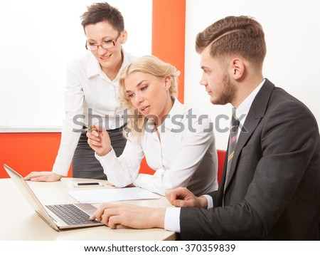 Man and woman working together on laptop in office at desk - stock photo