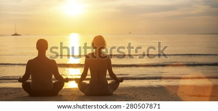 Man and woman yoga silhouettes meditating on Sea coast during the sunset. - stock photo