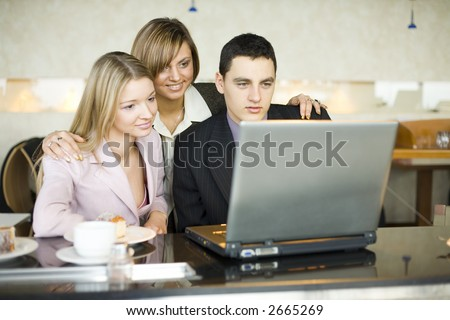 Man and Women at Cofe Table With Laptop. Short Depth of Focus (On Man's Face). - stock photo