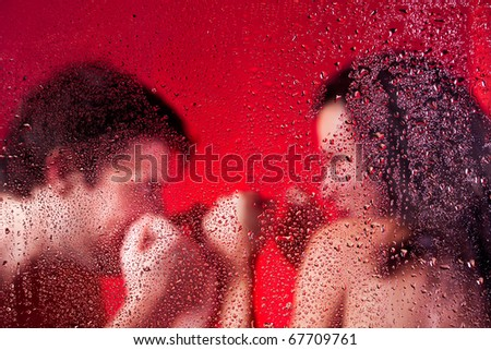 Man and women boxing naked behind wet glass