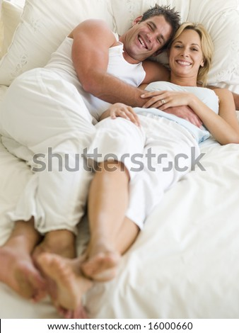 man and women laying on a bed - stock photo