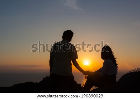 Man and women on top of the mountain viewing sun rise from sea - stock photo