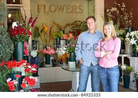 Man and women standing outside florists - stock photo