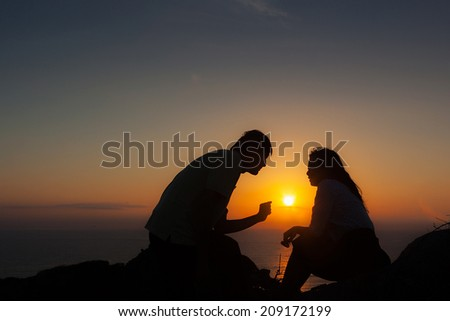Man and women talking on top of the mountain, sun rise from sea behind - stock photo