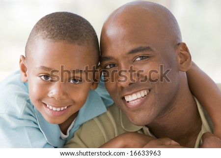 Man and young boy embracing and smiling - stock photo