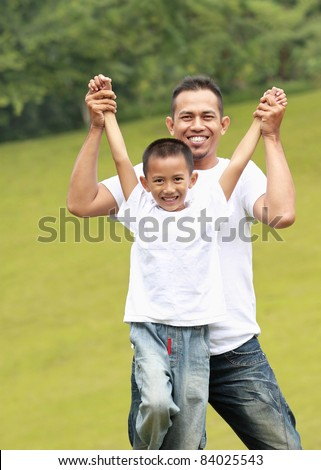 Man and young boy outdoors playing airplane smiling in the park - stock photo