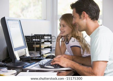 Man and young girl in home office with computer smiling - stock photo