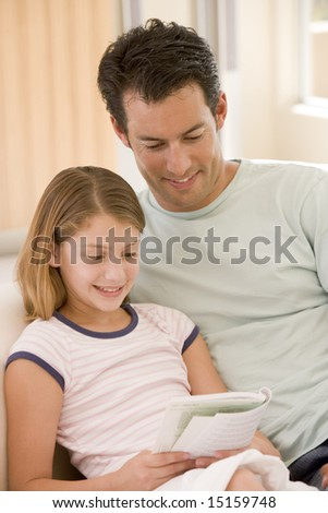 Man and young girl in living room reading book and smiling - stock photo
