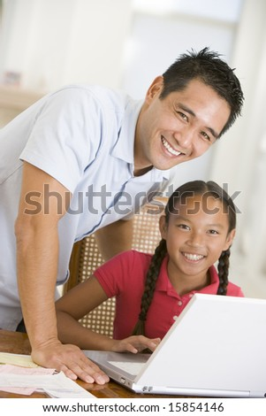 Man and young girl with laptop in dining room smiling - stock photo