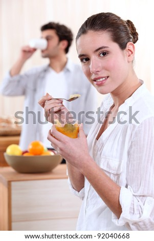 Man and young woman having breakfast - stock photo